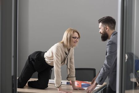 Office romance concept. Sexy secretary seduce boss in office. Businesswoman on desktop look at bearded businessman. Man under woman domination, matriarchy. Sexual flirt at work