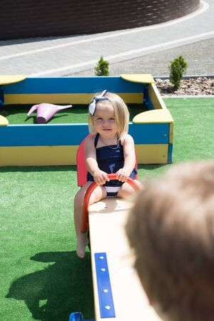 Just play. Small children with blond hair on seesaw. Small brother and sister enjoy playing together. Girl and boy haircut styles. Hair salon for children. Bring more creativity and style to hair 版權商用圖片