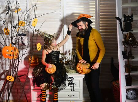 Girl and bearded man with cheerful faces in carnival room