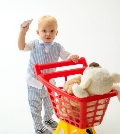 little boy go shopping with full cart. little boy child in toy shop with credit card. savings on purchases. shopping for children. happy childhood and care. It is bargain. Online store. Need purchase