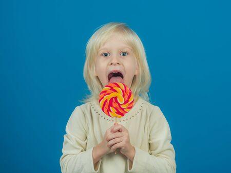 Happy childhood food. Little girl hold lollipop on stick. Little child with sweet lollipop. Happy candy girl. Enjoying the enormous flavor