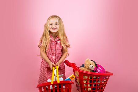 Shopping for value. Small girl happy smiling in shop. Happy small shopper. Little girl shopping. Little shopaholic with shopping cart. Retro throwback
