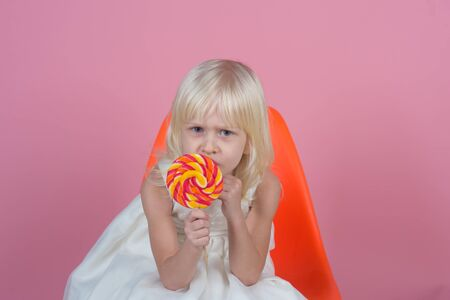No child can resist these exciting yummy treats. Small girl hold lollipop on stick. Small child with sweet lollipop. Happy candy girl. Happy childhood food Stock Photo