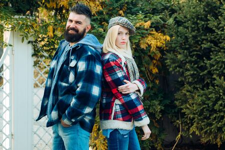 Lumberjack style. Couple wear checkered clothes nature background. Man bearded hipster and girl wear kepi hat. Checkered style. Couple handsome bearded hipster and fashion girl. They have own style Stock fotó