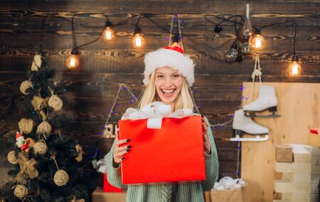 Beautiful Woman with christmas box gif at Home. Beauty Model Girl in Santa Hat on home design decorate. Friendly and joy. Happy people. Stock Photo