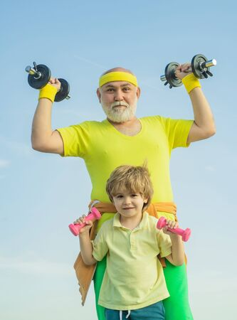 Grandfather and child in gym working out with weights. I love sport. Body care and healthcare. Senior man and child in family health club.