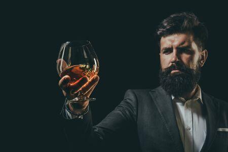 Hombre de negocios barbudo en traje elegante con copa de coñac. Concepto de bebida de lujo. Camarero de hombre sosteniendo una copa de coñac.