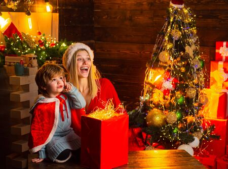 Child boy and mother with a Christmas mood. Young Baby Sitter plays with a little boy. 4-5 years boy pointing up with index fingers, enjoying beautiful stars and making question. Stock Photo