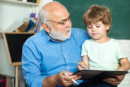 Grandfather talking to grandson. Family generation and relations concept. Happy cute clever boy and old tutor with book. Funny little child having fun on blackboard background.