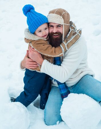 Little son hugs his dad on winter holiday. Daddy and boy smiling and hugging. Father and son play in winter clothes. Winter scene on white snow background. Banque d'images - 129019977