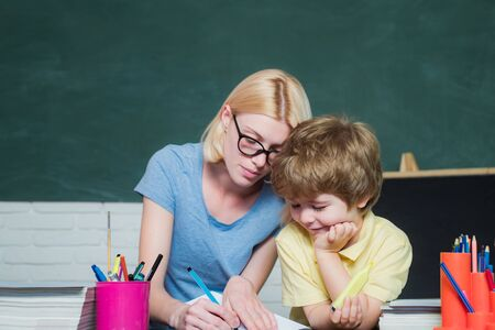 Funny little child and young female teacher having fun on blackboard background. Female teacher and schoolboy in class at school. Great study achievement.
