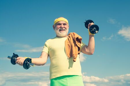 Grandfather exercising with dumbbell. Sport for senior man. Senior man lifting weights. Reklamní fotografie
