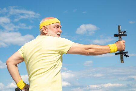 Elderly man after her workout. Senior sportman exercising with lifting dumbbell on blue sky background. Isolated, copy space.