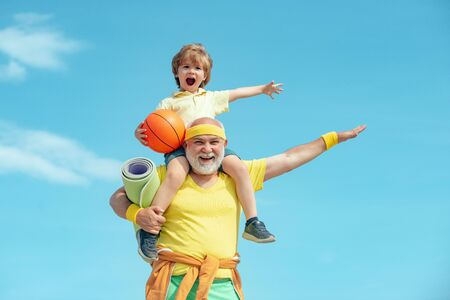 Familiensport. Porträt eines gesunden Vaters und Sohnes, die über Hintergrund des blauen Himmels ausarbeiten. Glückliche liebevolle Familie. Standard-Bild