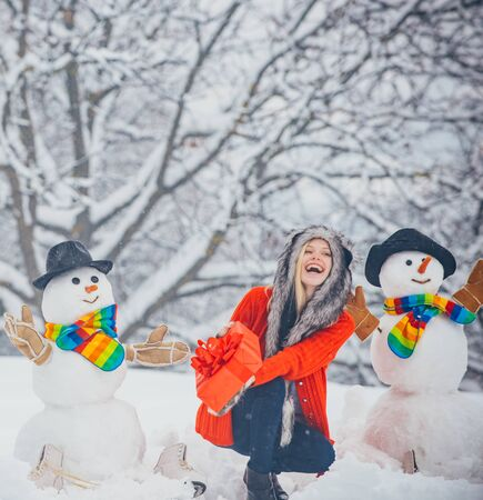 Funny snowmen. Merry Christmas and Happy Holidays. Christmas preparation - funny girl make snowman. Snowman and funny girl in the snow. Standard-Bild - 129020812