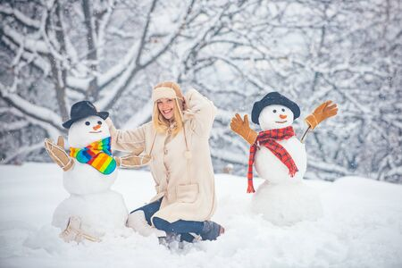 Happy winter time. Winter concept. Snowman and funny girl the friend is standing in winter hat and scarf with red nose.