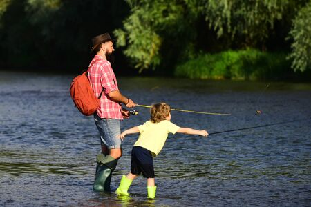 Father and Son fishing - Family Time Together. Anglers. I love our moments in the countryside - remember time. Father with his son on the river enjoying fishing holding fishing rods. Banco de Imagens