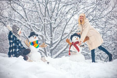 Hipster Girls friends playing with Snowman on snow Winter landscape. Christmas preparation - funny girls make snowman. Funny winter people Portrait.