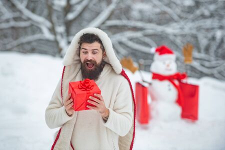 Merry Christmas and Happy new year. Joyful Father hold gift and Having Fun with snowman in Winter Park. Holly jolly swag Christmas and noel.