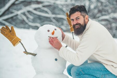 Funny snowmen. Happy smiling man make snowman on sunny winter day. People in snow. Snowman. Handsome Winter Man with snowman in frosty winter Park. Standard-Bild - 129020834