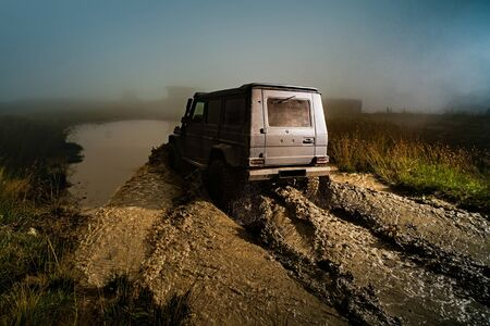 Offroad car on bad road. Water splash in off-road racing. Wheel close up in a countryside landscape with a muddy road. Stock Photo