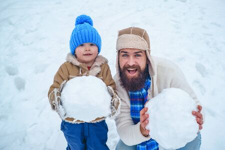 Dad and baby son playing together outdoors. Winter father and son. Happy child playing with snowball against white winter background. Winter scene on white snow background.