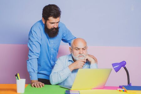 Two businessmen in an office while working together behind a laptop computer. Businessman read news in internet.