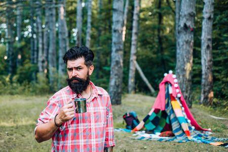Homemade tent - hut. Handsome bearded man having fun in adventure Park.