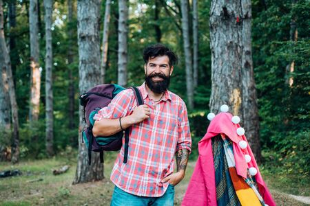Homemade Tent Camping for free man. Summer camp and nature tourism. Go Ape Adventure. Happy man in summer.