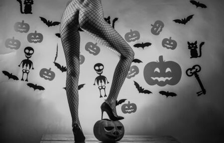 Beautiful erotic woman posing nude on halloween background. Great ass and pumpkin. Advertisement concept. Sexy pumpkin butt. Sexy Witch vampire concept. Carved Pumpkin - funny concept Stock Photo - 129124874