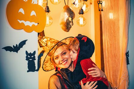 Happy Halloween. Mother and son with witch costumes and witch hats. The Most Popular Candy for Halloween. Halloween pumpkin head jack lantern with burning candles.
