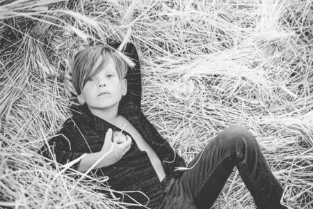 Fair-haired boy lies on hay background and eats an apple. Portrait of a cheerful boy lying in a hay. Little boy advertises natural products. Cute boy on an autumn holiday in the village.