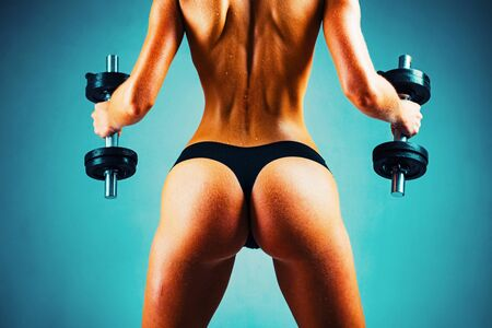 Attractive female doing biceps curl with dumbbells in the gym. Female fitness model. Healthy woman doing workout. Banco de Imagens