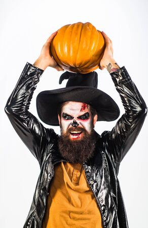 Devil man with bloody face. Scary face man with horror Make up holding Pumpkin head jack lantern. Vampire Halloween Concept.