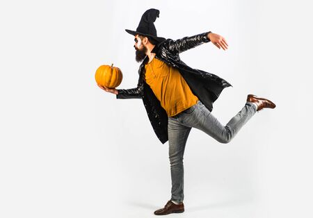 Vampire man with bloody eyes. Scary hipster with beard in Halloween hat. Scary face man with horror Make up holding Pumpkin head jack lantern. Scary face. White background isolated.