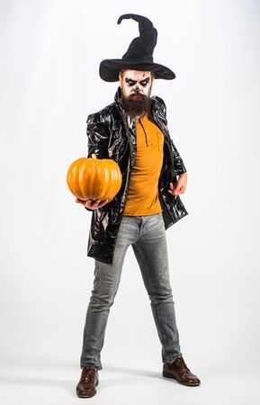 Young man with witch hat dressed as vampire for Halloween party - full length. Bearded man dressed like Halloween monster. White background isolated. Halloween bearded man with blood make-up. Stockfoto