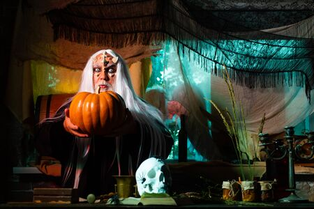 Horror with scary Halloween demon man. Devil vampire man. Halloween concept. Scary Halloween man in hat - studio shot close-up. Halloween demon.