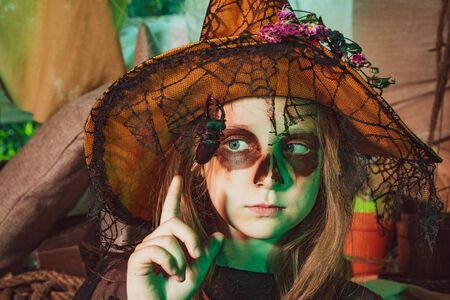 Kid eyes with skull make up. Little Witch. Funny child girl with skeleton costume holding skull and eating candies. Happy funny little girl with Halloween pumpkin make funny face.