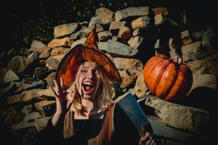 Happy Halloween witch with pumpkin. Halloween horror concept. Woman witch with pumpkin. Halloween Sexy Witch girl portrait.