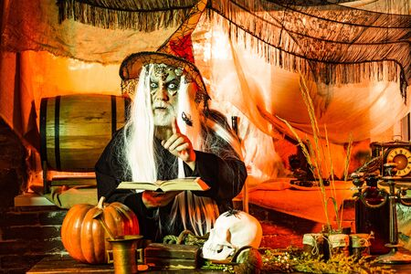 Design for Halloween banner. Halloween holiday celebration - Man demon on black background. Halloween bearded man with blood make-up.