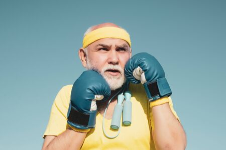 Handsome elderly man practicing boxing kicks - close up portrait. Healthy fighter senior old man boxing gloves. Grandfather doing boxing training in morning.