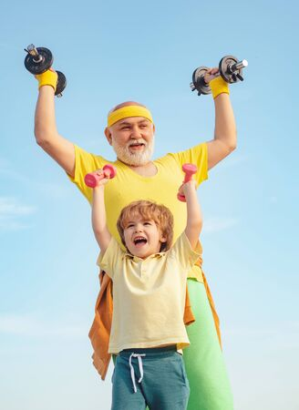 Sports education. Father and son spotting. Healthy family lifestyle. Boy is doing exercises to develop muscles. Follow grandfather.