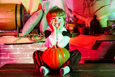 Boy with pumpkin dressed like vampire for Halloween party. Witch children with trick or treat. Halloween holidays concept. Standard-Bild - 129258219