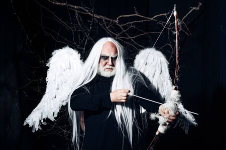 Man in angel costume. Angel man with feather white wings and gift. Satan on Hell. Bearded old man dressed like Halloween monster. Man evil with horns.