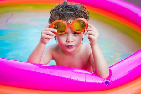 Child boy and best swimming pool. Child swimming pool. Children fun. Child water toys. Cute kid relaxing on swimming pool.