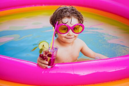 Kids Swimming Pool Concept. Summer vacation. Kids learn to swim. Cocktails drinks. Happy little boy playing in swimming pool outdoor on hot summer day. Vacation at Paradise.