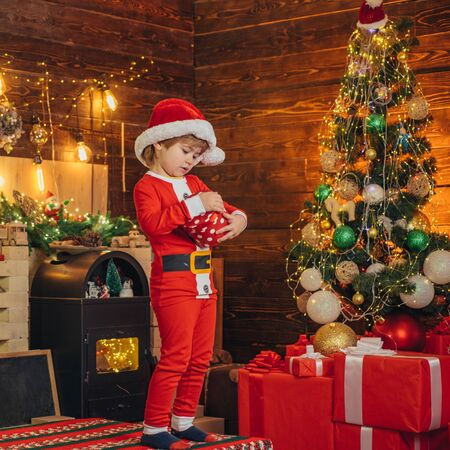 Santa boy little child celebrate christmas at home. Family holiday. Boy cute child cheerful mood play near christmas tree. Merry and bright christmas. Opening gift. Lovely baby enjoy christmas Standard-Bild - 129258191