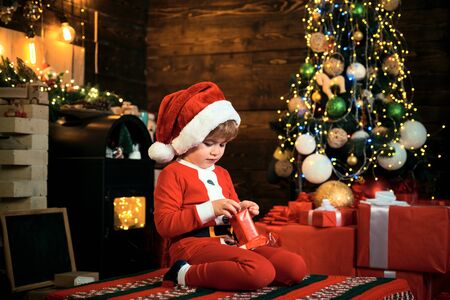 Merry and bright christmas. Opening gift. Lovely baby enjoy christmas. Santa boy little child celebrate christmas at home. Family holiday. Boy cute child cheerful mood play near christmas tree Standard-Bild - 129258198