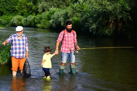 Portrait of happy little son, father and grandfather - three generations of men fishing on river. Happy fathers day. I love fishing.
