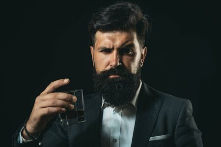 Luxury alcohol drink. Degustation of elite alcohol. Confident bearded man in black suit with glass of whisky in loft.
